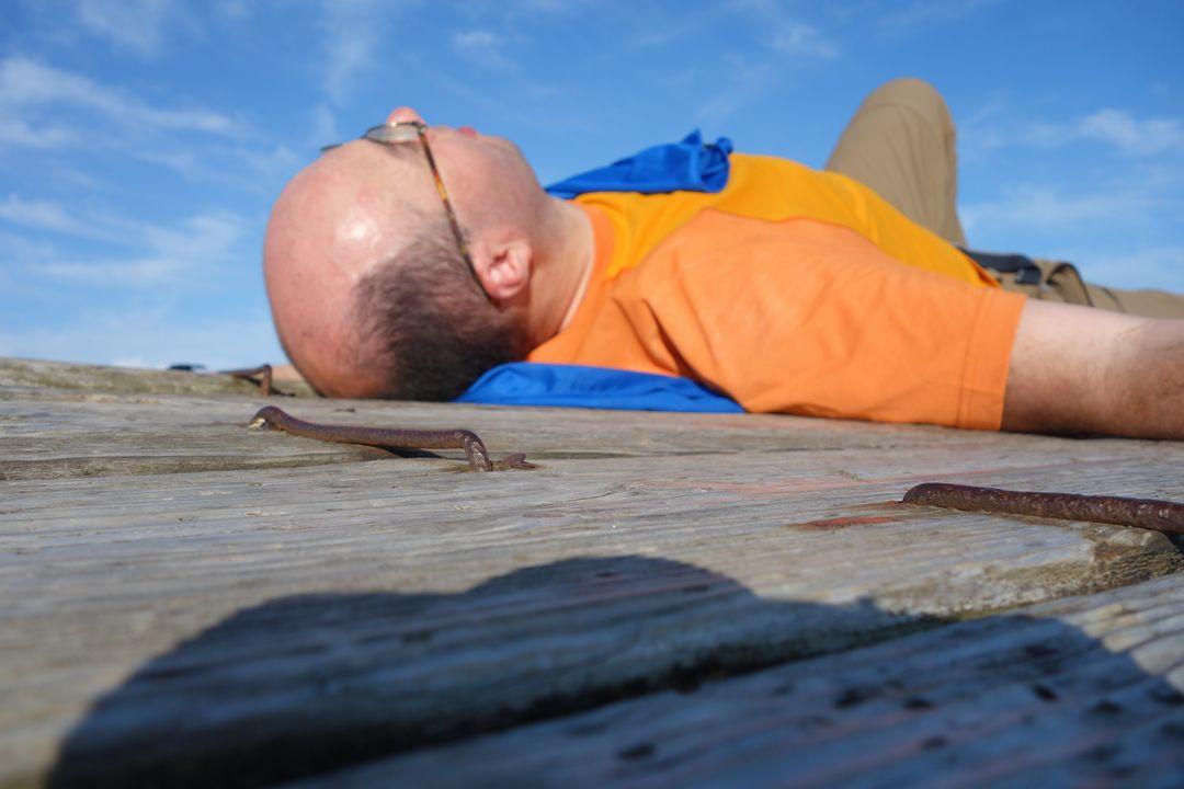 ベンチの上に倒れこむ登山者