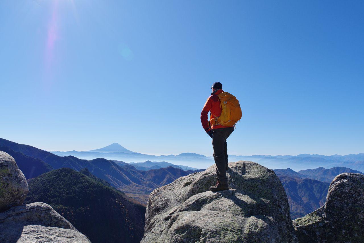 瑞牆山の岩の上に立つ登山者